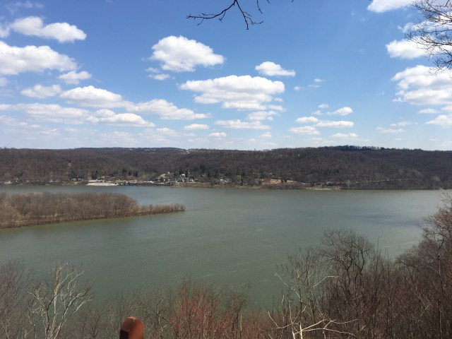 A bright blue sky, white puffy clouds and a gray wide river.