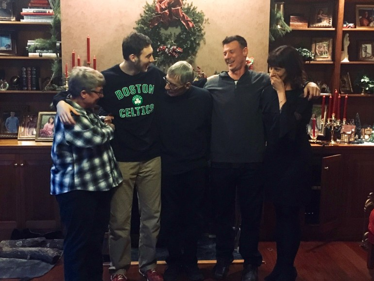 Two men and two women flanking an older gentleman, and laughing together