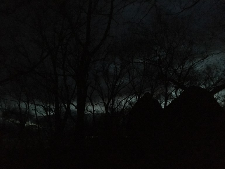 Dark trees and rocks silhouetted agains a sliver of silver grey sky