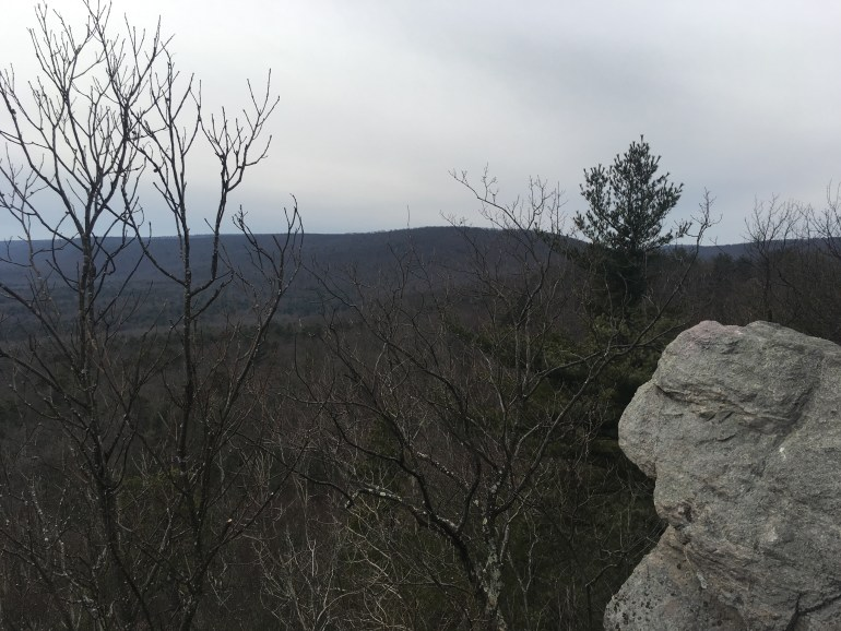 An overcast winter sky above a valley, with a large rocky outcrop in the foreground