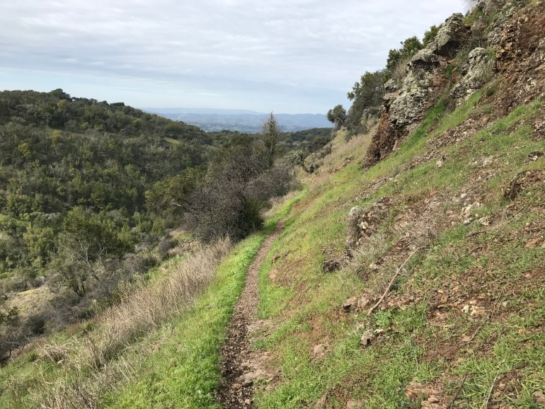 A dirt trail cuts through the hillside, haze covered mountains visible in the far distance