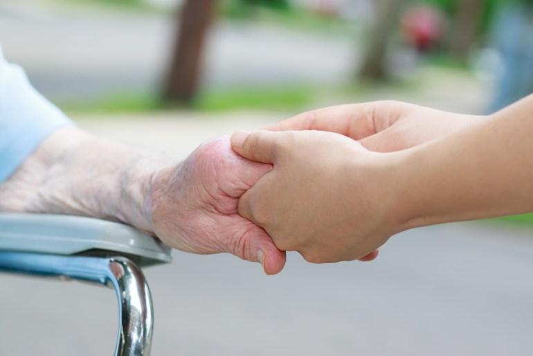 A closeup of a young caregiver's hand entwined in the hand of an older person