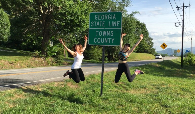 Two women jumping beside the Georgia State Line sign