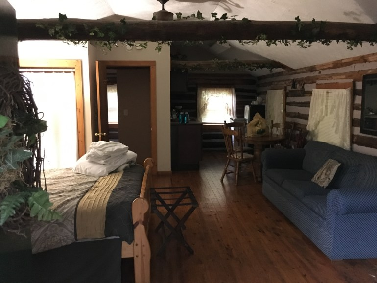 Inside a cabin, a bed, blue sofa, small kitchen table  and bathroom.