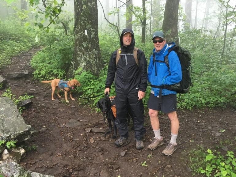 Two men in rain gear on a hiking trails