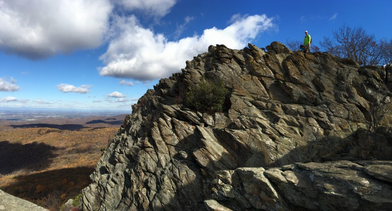 """A man and dogs on top of a jagged """"humpback"""" rock, white puffy clouds and a bright blue sky overhead"""