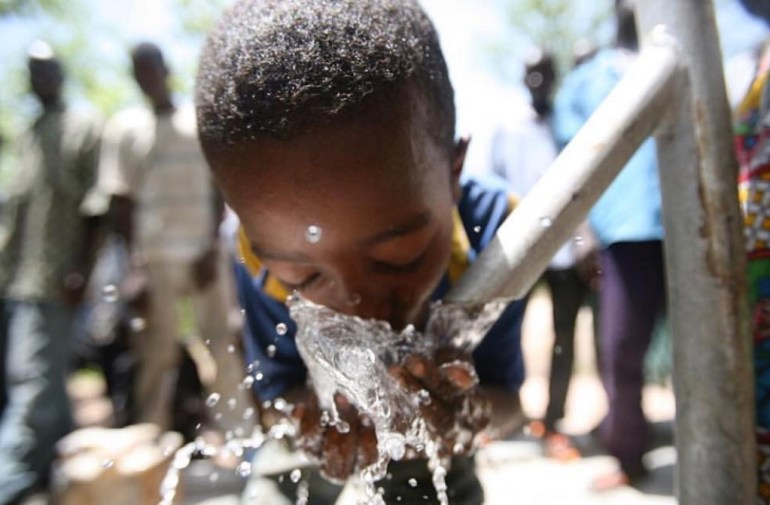 Young African boy drink fresh water from a pump.