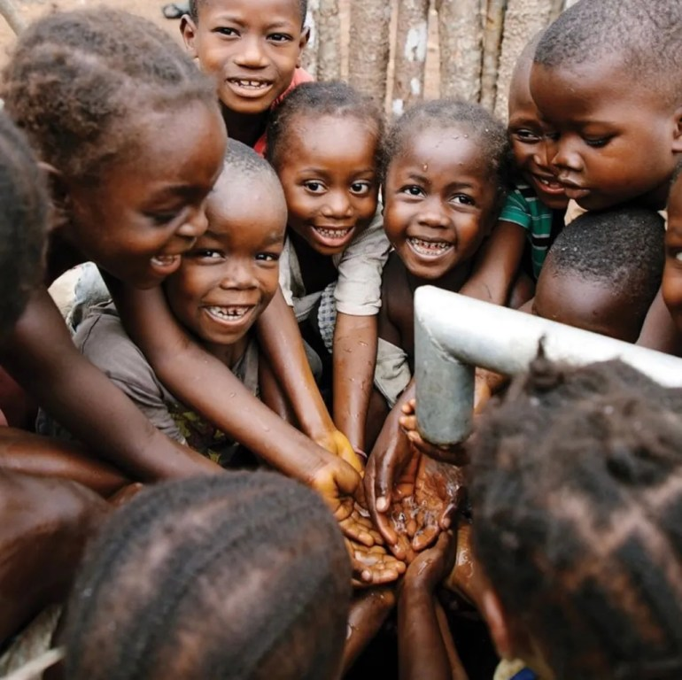 Laughing African children gathered with their hands under a spigot of running water.