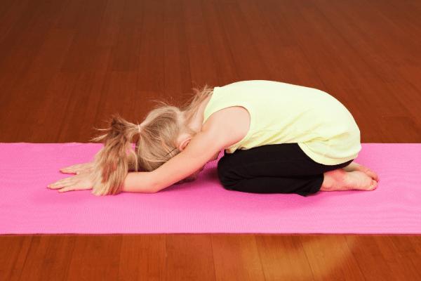 blond toddler yogi in child's pose
