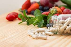 image of vitamins and an assortment of fruits and vegetables on a wooden tabletop