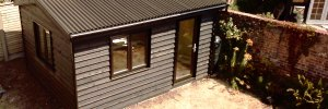 Black Cladded Pitched Roof Garden Room in Fishbourne / Chichester