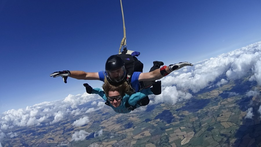 Beckie flying through the sky strapped to her instructor having jumped out of the plane
