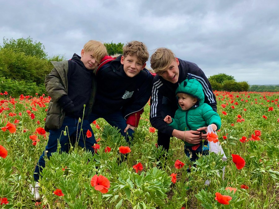 Beckie's 4 boys having fun and smiling at the camera in a poppy field
