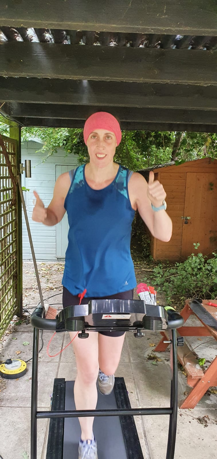 Emily running her marathon on a treadmill, smiling and giving a big thumbs up