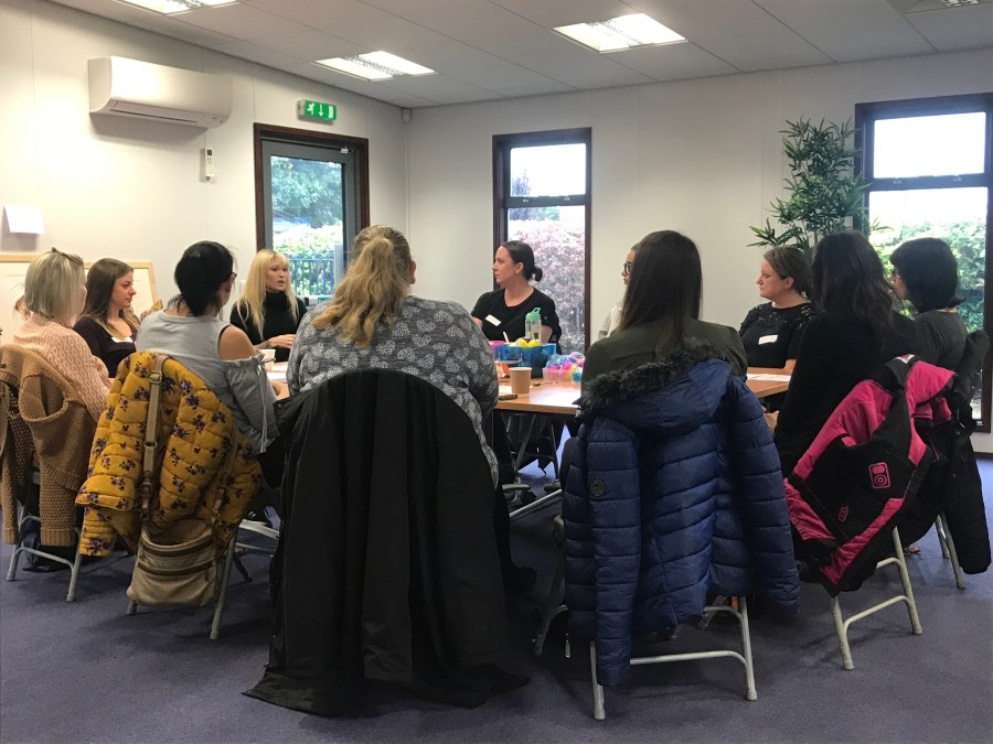 Adults sat around a table at a SPACE support group