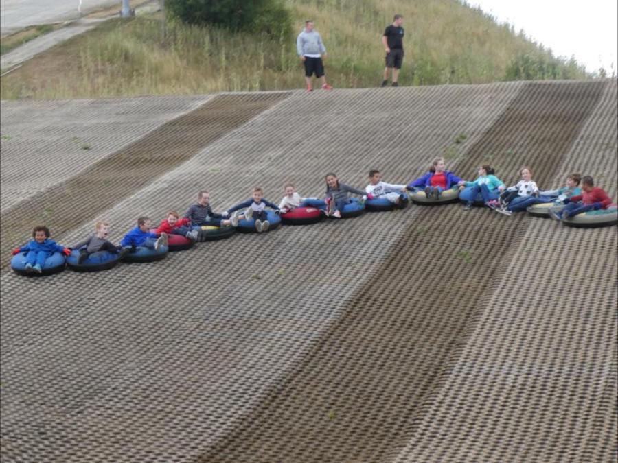 children sitting in doughnuts sliding down a slope