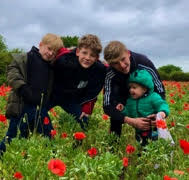Beckie's 4 boys smiling at the camera and each other in a poppy field