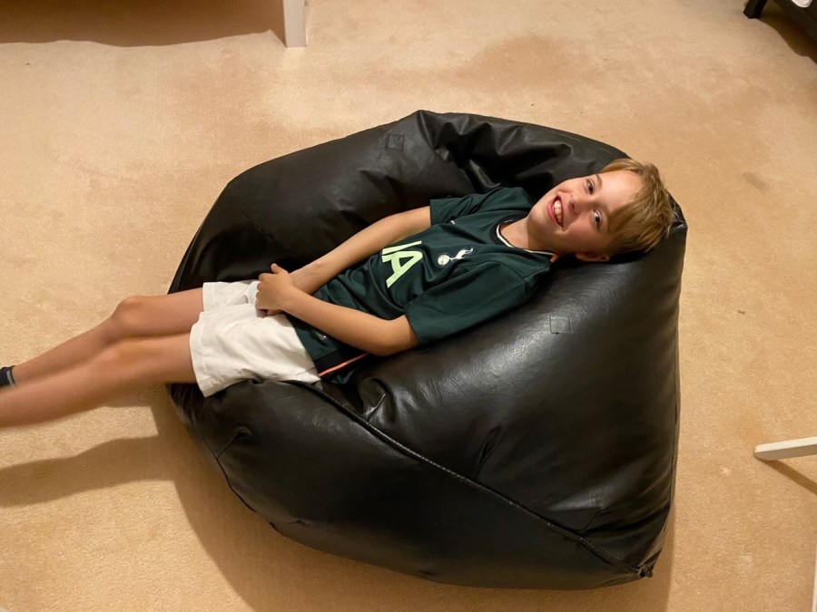 Child relaxing on a bean bag that can be borrowed for free from Lending SPACE