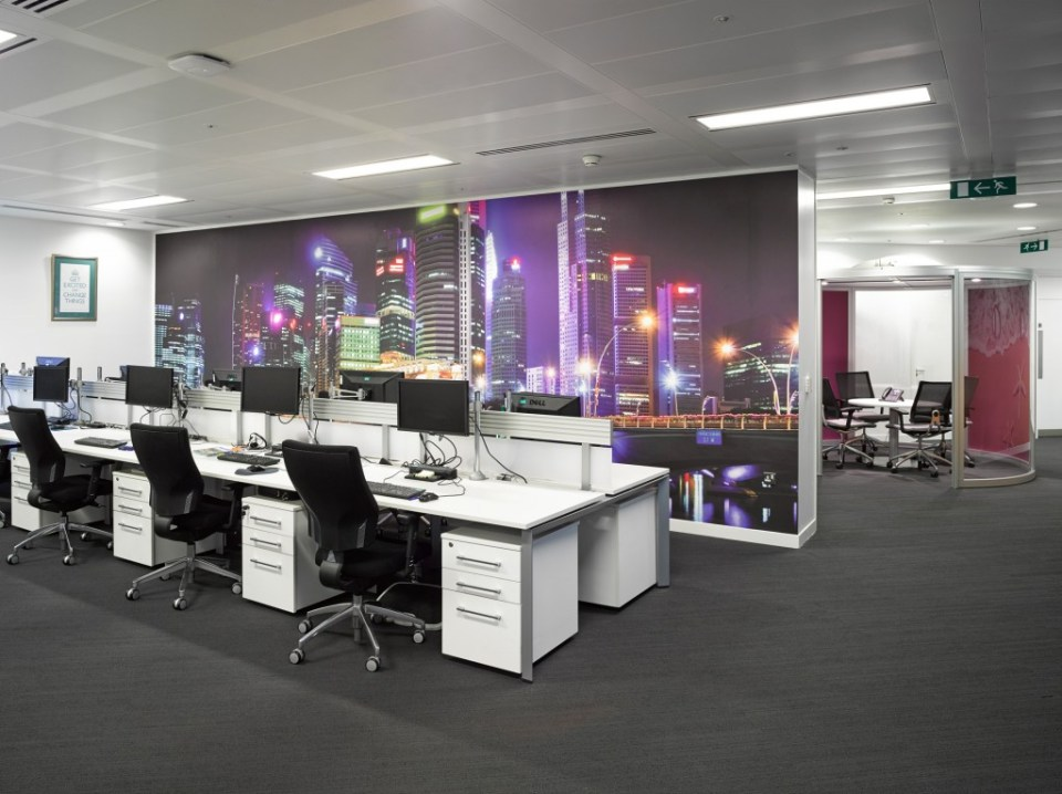 Picture of Thomas Cook HQ back-to-back bench desking, featuring monitor arm ergonomics, slat wall railing. Also shows digital wallpaper graphics and meeting pod