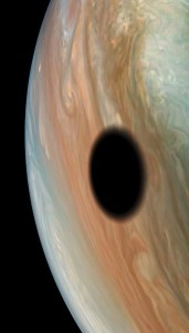 Jupiter's volcanically active moon Io casts its shadow on the planet in this dramatic image from NASA's Juno spacecraft. As with solar eclipses on the Earth, within the dark circle racing across Jupiter's cloud tops one would witness a full solar eclipse as Io passes in front of the Sun.