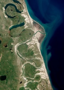 The sinuous Horton River flows in a curved line from top to bottom of this image, breaking free around the centre and fanning out into the sea on the right-hand side.