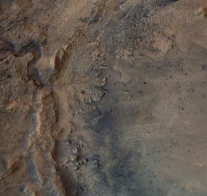 An ancient river delta spreads red, orange and brown sand from the old river bed (right) to the basin (left) in Jezero Crater on Mars.