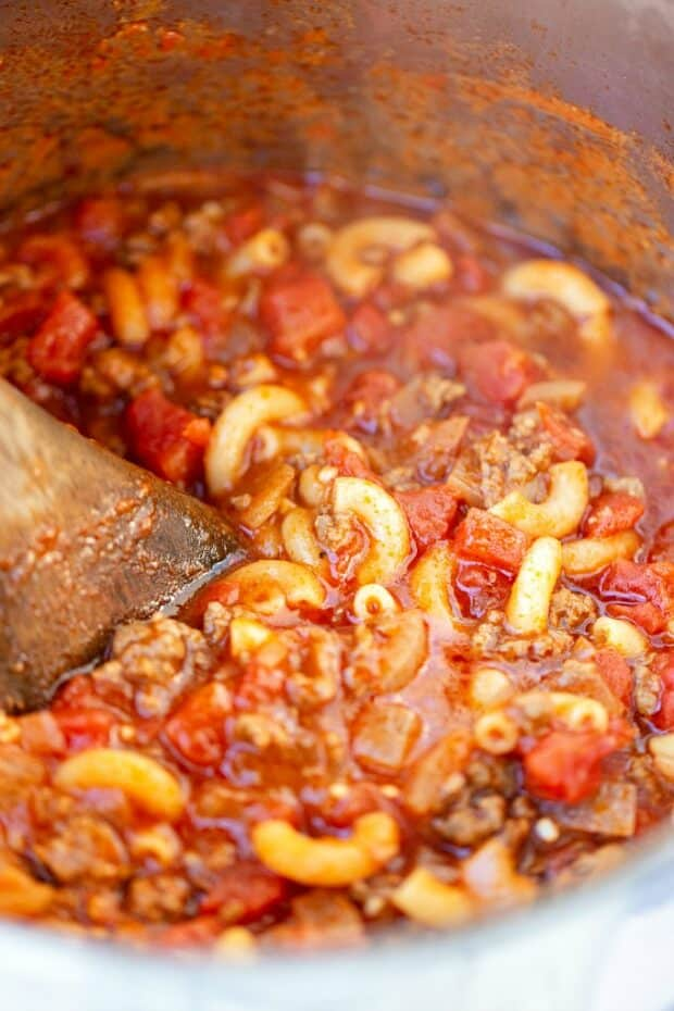 pot of goulash being stirred by wooden spoon