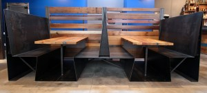 These custom booths were designed to look as though they were bent from a single piece of steel. (They're actually quite comfortable.)