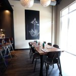 The community table, crafted from a single slab of cherry wood. The chalkboard features a drawing of an agave plant.