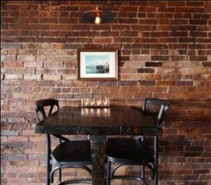 Bar vignette. SPACE designed and built the rustic bar-height tables. A Karl Bodmer landscape is featured at each table.
