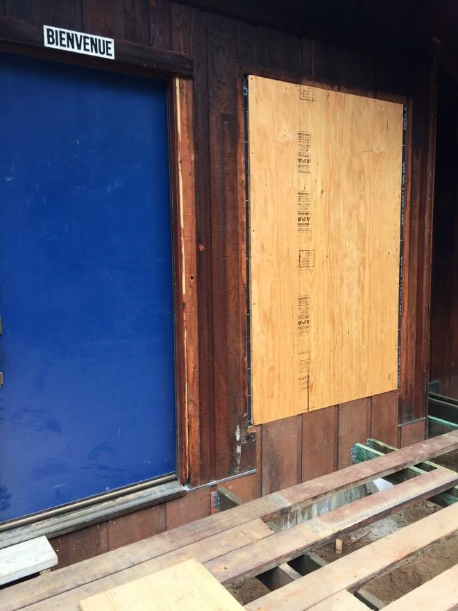 Front door and bathroom window with part of the deck.