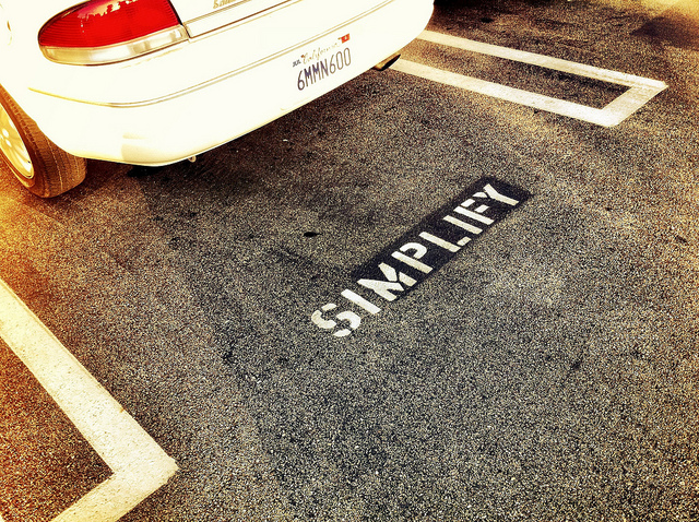 Simplify written on ground behind car
