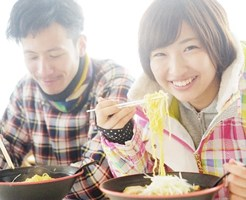 スキー場でラーメン食べるカップル