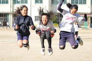校庭で運動する女子