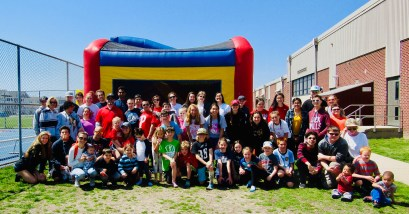 Ocean County SEPAG members pose in front of a bounce house on a sunny day