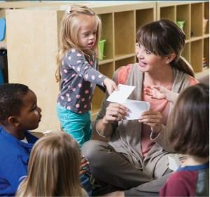 teacher assisting small child student