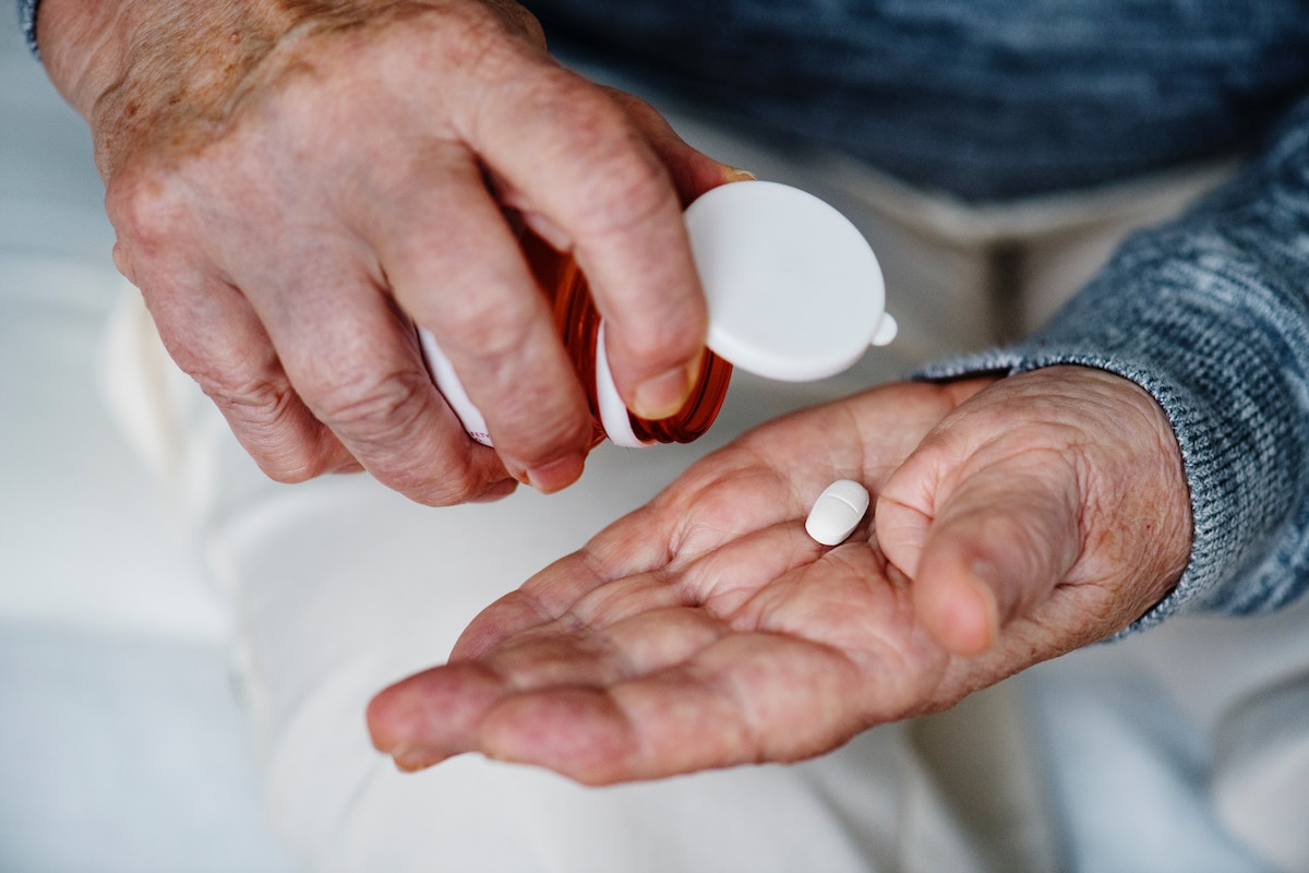 Picture of an older man holding a pill bottle with a white pill in his one hand. Picture is being used for a blog about medication management.