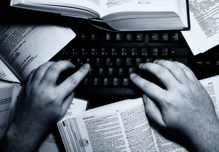 Hands over keyboard with dictionary