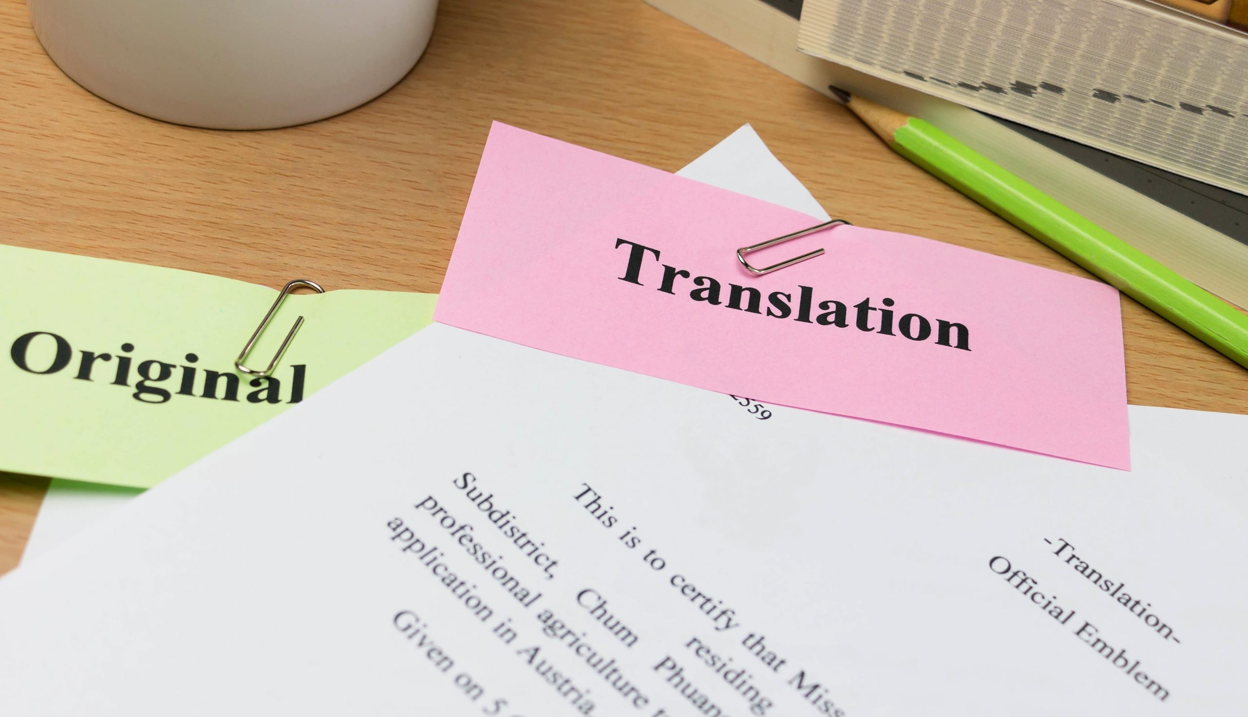 """Documents on desk clipped with tabs """"Original"""" and """"Translation"""