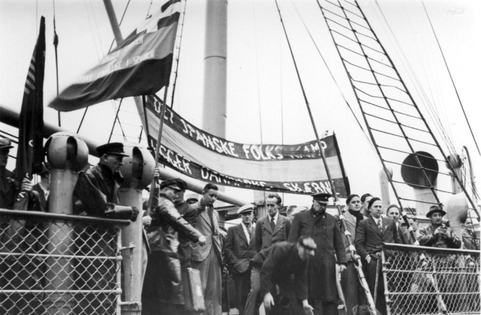 """Hjemsendelsen af de Internationale Brigader og tiden der fulgte: S/S Bernstorffs ankomst til Esbjerg Havn med de 91 frivillige, november 1938. Teksten på banneret er som følger: """"I det spanske folks kamp ligger Danmarks skæbne"""""""