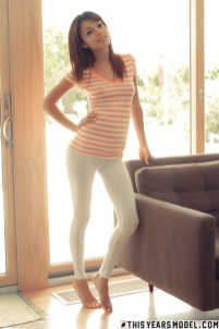 Ashley Doll posing at home in white leggings and a striped t-shirt