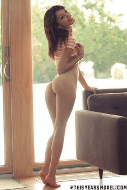 Spankable Ashley Doll shows off her bare ass by the window
