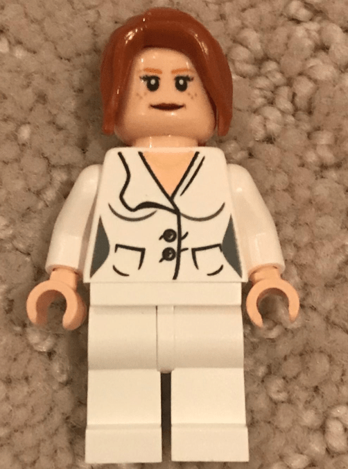Lego figurine with long brown hair wearing a white pantsuit that is cinched in to show hips and cleavage