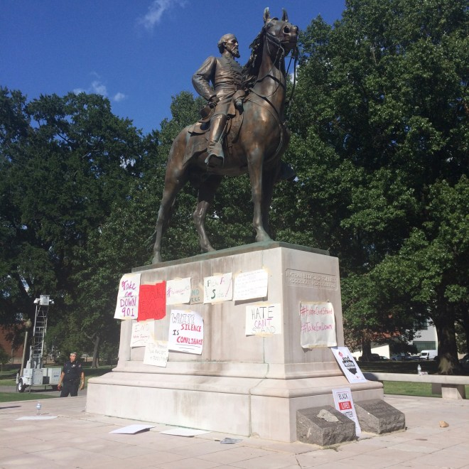 Figure 1 shows a photo of the Forrest statue covered in protest signs.
