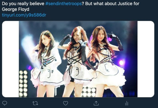 "A screenshot of a Tweet paired with a photo. The tweet reads: ""Do you really believe #SendInTheTroops? But what about Justice for George Floyd?"" The photo is of three Korean pop stars posing on stage, each smiling. They wear white dresses and black gloves; their hair is dark, long, and down. Purple stage lights illuminate them."