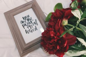 red roses beside a frame that says 'you're the perfect type of weird'