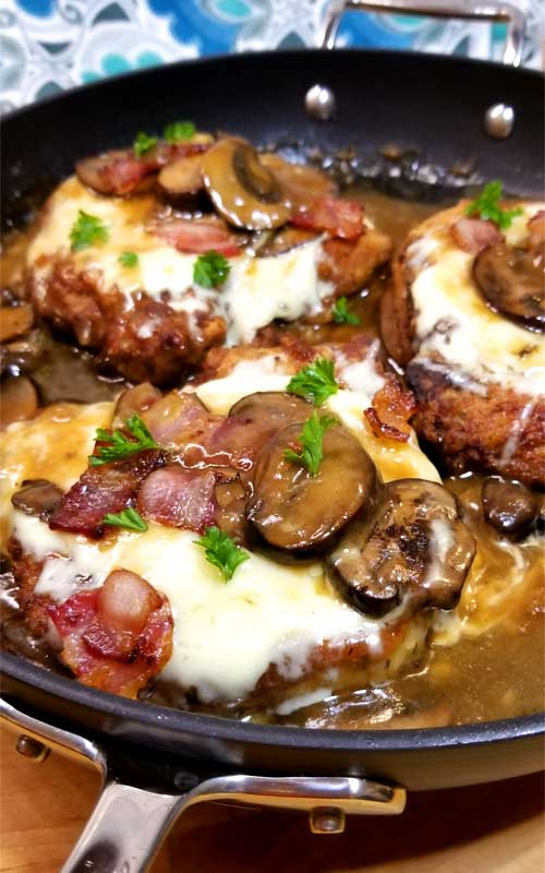 Fontina Pork Chops with Marsala Mushroom Gravy - Juicy flavorful pork chops blanketed with melted fontina cheese and covered with a garlicky Marsala mushroom gravy. An easy delicious home cooked meal with restaurant quality.