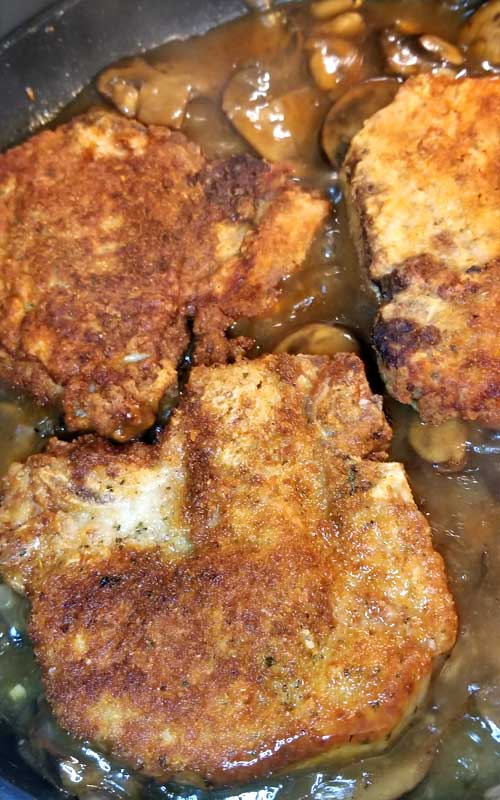 Fontina Pork Chops with Marsala Mushroom Gravy - Juicy flavorful pork chops blanketed with melted fontina cheese and covered with a garlicky Marsala mushroom gravy. An easydelicious home cooked meal with restaurant quality.