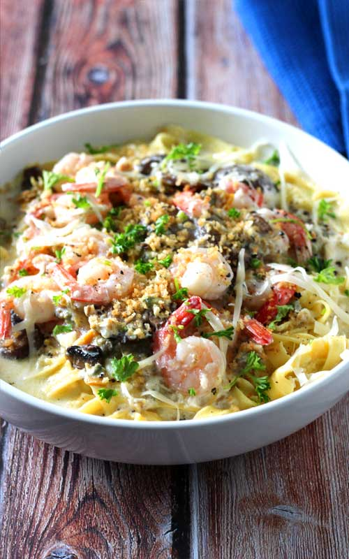 When shrimp, crab, clams, and mushrooms come together in a luscious creamy, cheesy garlic sauce over fresh pasta, you get this delectable Seafood Alfredo Fettuccine!