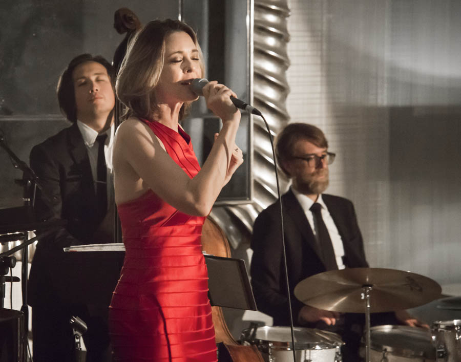Woman in a red dress sings with eyes closed in front of her band